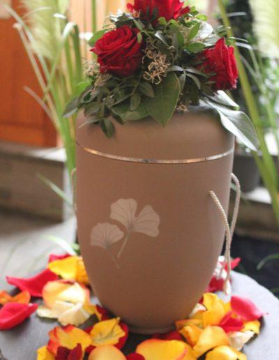 Urnenschmuck mit Rosenblättern und Gesteck mit roten Rosen